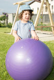 Toddler boy playing with big ball Stock Image