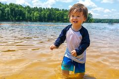 Toddler boy playing in a lake on a summer day Stock Photography