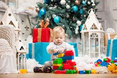 Toddler boy playing with blocks at Christmas tree Royalty Free Stock Image