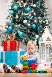 Toddler boy playing with blocks at Christmas tree Stock Photo