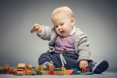 Toddler boy playing with building blocks. Toddler boy playing with building blocks, having fun and developing his creativity stock image