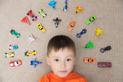 Toddler boy playing with car collection on carpet. Transportation,airplane, plane and helicopter toys for children Royalty Free Stock Photography