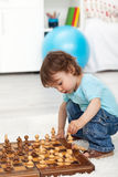Toddler boy playing with chess pieces Royalty Free Stock Photography