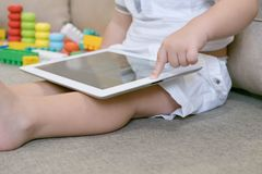 Toddler boy playing with digital tablet on couch at home. little boy toddler sitting and watching plays in the tablet royalty free stock image