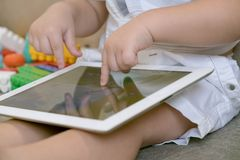 Toddler boy playing with digital tablet on couch at home. little boy toddler sitting and watching plays in the tablet royalty free stock photos