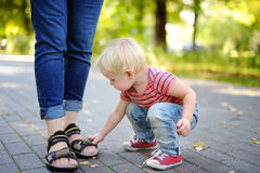 Toddler boy playing with footwear Stock Image