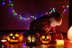 Toddler boy playing with halloween pumpkins indoors. Halloween party for little kid at home Royalty Free Stock Image