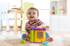 Toddler boy playing indoors with sorter toy sitting on soft carpet. Toddler baby boy playing indoors with sorter toy sitting on soft carpet Royalty Free Stock Photo