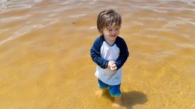 Toddler boy playing in a lake on a summer day Stock Photo