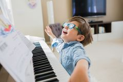 Toddler boy is playing piano at home royalty free stock photo