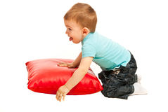 Toddler boy playing with pillow. Toddler boy laying with a red pillow isolated on white background Royalty Free Stock Images