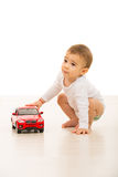 Toddler boy playing with red car Royalty Free Stock Photos