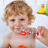 Toddler boy playing with soap bubbles in bathtub Stock Images