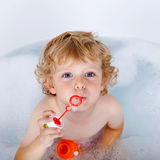 Toddler boy playing with soap bubbles in bathtub Royalty Free Stock Photo