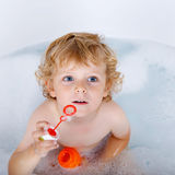Toddler boy playing with soap bubbles in bathtub Royalty Free Stock Image