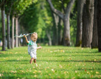 Toddler boy playing with toy glider in park Royalty Free Stock Photography