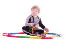 Toddler boy playing with a toy train Royalty Free Stock Image