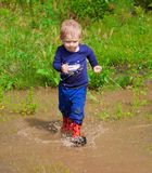 Toddler boy playing in water puddles Royalty Free Stock Photo