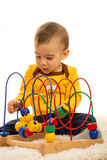 Toddler boy playing with wooden toy Stock Images