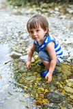 Toddler boy plays in flashy river Stock Image