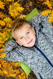 Toddler boy portrait lying in autumn Royalty Free Stock Images