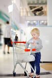 Toddler boy putting purchase in little shopping cart Stock Photography