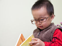 Toddler Boy Reading Book. And wearing a big glasses Stock Photography
