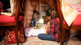 Cute toddler boy reading book in tepee tent in bedroom. Toddler boy reading book in tepee tent in bedroom Royalty Free Stock Photography
