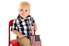 Toddler boy in a red chair holding an American flag Stock Image
