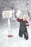 Toddler boy with Reindeer in snow Stock Photos