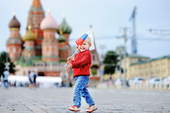 Toddler boy running with russian flag. Cute toddler boy running with russian flag with Red Square and Vasilevsky descent on background stock photos