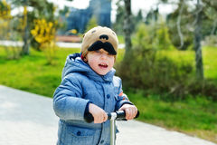 Toddler boy on the scooter Stock Image