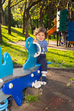 Toddler boy in seesaw in a sunny day Royalty Free Stock Image