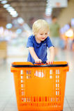 Toddler boy with shopping cart in a food store or a supermarket. Royalty Free Stock Photography