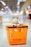 Toddler boy with shopping cart in a food store or a supermarket Royalty Free Stock Image