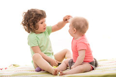 Toddler boy showing an egg to a baby girl Royalty Free Stock Photo