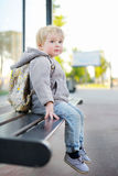Toddler boy sitting on bench on bus stop Royalty Free Stock Image