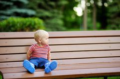 Toddler boy sitting on a bench Royalty Free Stock Photos