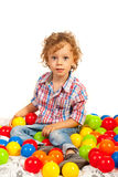 Toddler boy sitting on colorful balls Stock Images