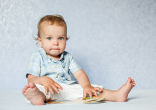 Toddler boy sitting considering the book Royalty Free Stock Images