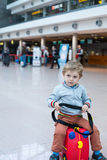 Toddler boy sitting on a suitcase at airport Royalty Free Stock Photography