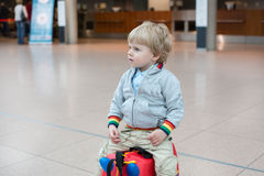 Toddler boy sitting on a suitcase at airport Stock Photos