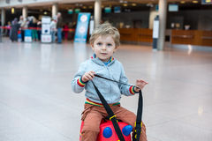 Toddler boy sitting on a suitcase at airport Royalty Free Stock Image
