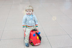 Toddler boy sitting on a suitcase at airport Stock Image