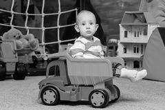 Toddler boy sitting in the toy truck Royalty Free Stock Image
