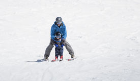 Toddler Boy Skis Downhill with the Help of His Father. royalty free stock images