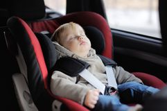 Toddler boy sleeping in car seat Stock Photo