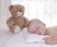 Toddler boy is sleeping on the pillow. Teddy bear is sitting near Stock Image
