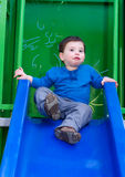Toddler boy smiling on a slide. Toddler boy smiling on a playground slide Royalty Free Stock Images