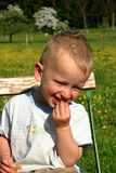 Toddler Boy snacking outside. Toddler boy sitting on chair outside eating a snack and smiling royalty free stock image